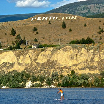 Paddleboarding in front of Penticton Sign on Munson Mountain